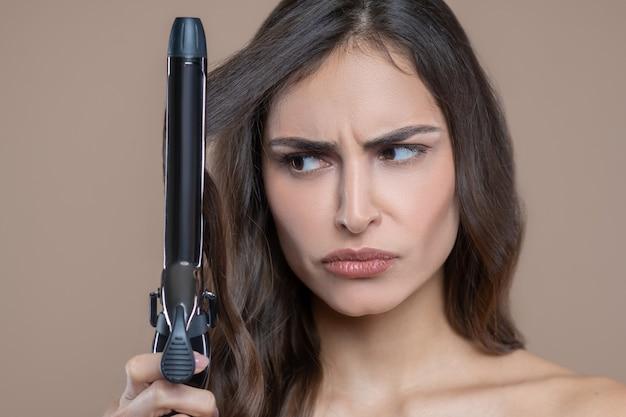 Щипцы для завивки. серьезное красивое лицо молодой длинноволосой женщины, недоверчиво смотрящей на щипцы для завивки завивки