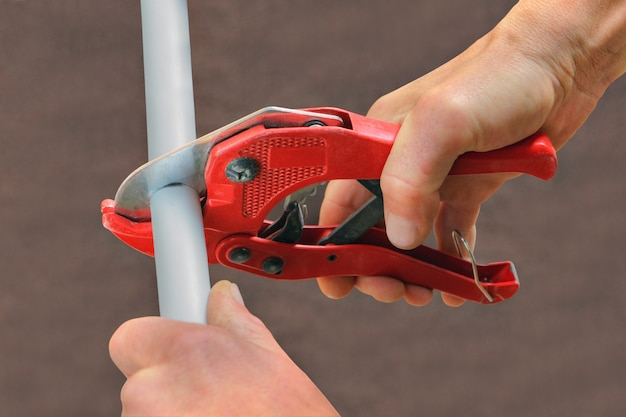 Using cutter for plastic pipes when repairing domestic water pipes, hand plumbing close-up.