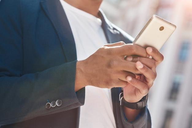 スマートフォンのクローズアップでインターネットを閲覧している街の通りに立っているデバイスの若い男を使用して