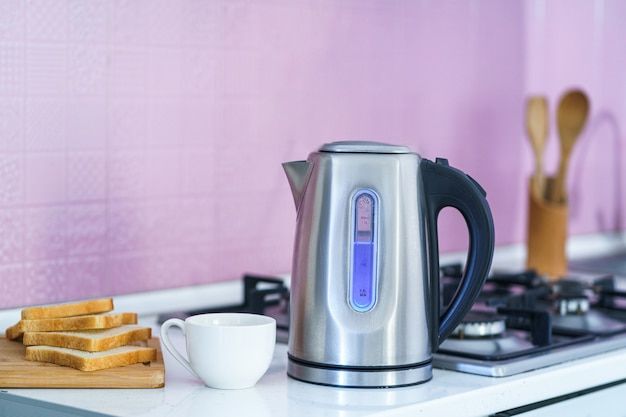 Using an electric kettle for brewing tea at home at kitchen