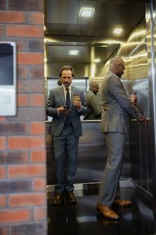 エレベーターを使う。ビジネスセンターでエレベーターを使用してコーヒーを保持しているスーツを着ているビジネスマン