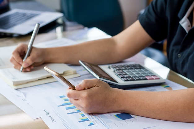 Using a financial calculator with writing make note and financial data on desk