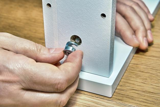 家具の組み立てにフラットパックハードウェアを使用し、カムロックナットを使用して引き出しを取り付けます。