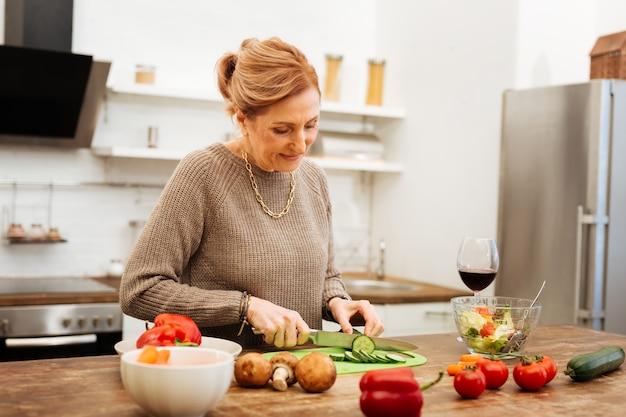 新鮮な野菜を使用。金属ナイフを運んでいる間、木製のテーブルで夕食の準備をしている集中した成熟した女性