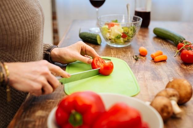 新鮮な野菜を使用。緑のボードに長い金属のナイフとトマトを刻んで運ぶ楽しい女性