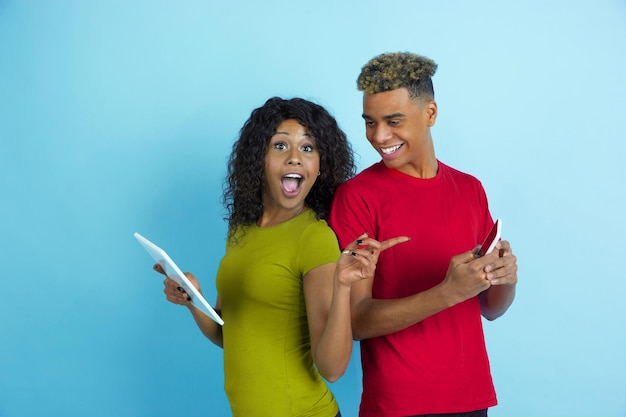 Using gadgets, laughting, pointing. young emotional african-american man and woman in colorful clothes on blue background.