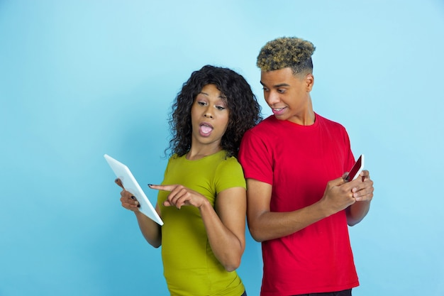 Using gadgets, laughting, pointing. young emotional african-american man and woman in colorful clothes on blue wall.
