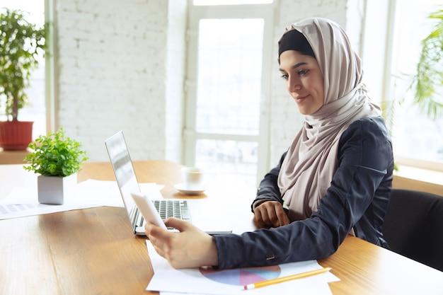 가제트 사용. 오픈스페이스나 사무실에서 일하는 동안 히잡을 쓴 아름다운 아라비아 여성 사업가의 초상화. 직업의 개념, 비즈니스 영역의 자유, 리더십, 성공, 현대적인 솔루션. 프리미엄 사진