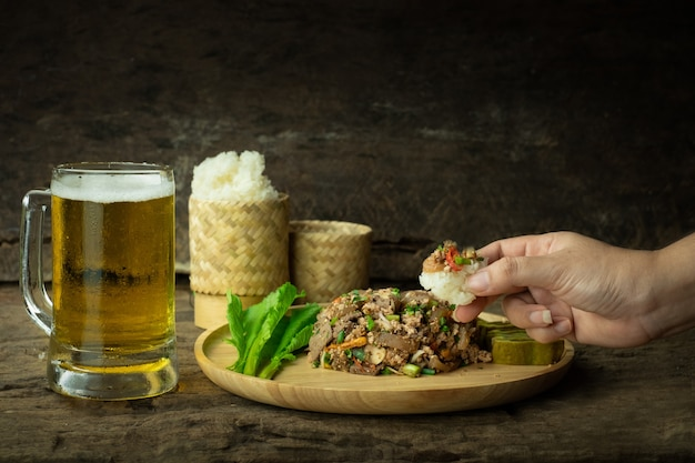 Using a hand to eat sticky rice and spicy minced pork salad with beer
