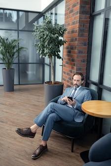 彼の電話を使用します。同僚を待っている間彼の電話を使用してひげを生やした繁栄しているビジネスマン