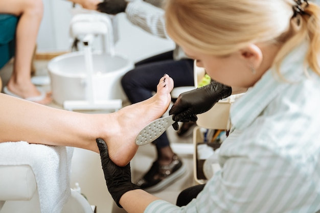 Using instruments. blonde-haired professional chiropodist using instruments making manicure