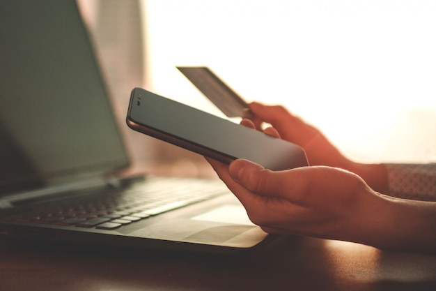 Using a laptop, credit card and mobile phone to buy and payment goods.