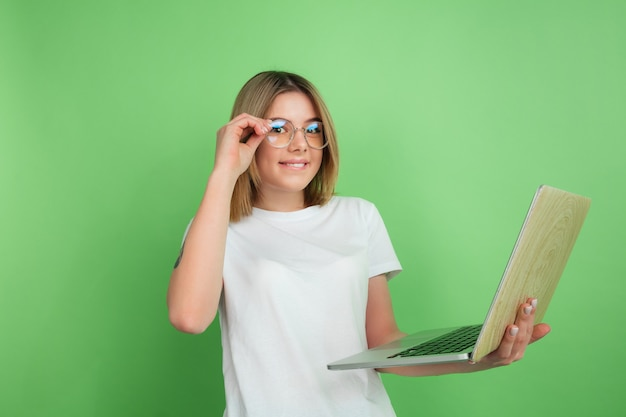 Using laptop emotional. caucasian young woman's portrait isolated on green wall. beautiful female model in white shirt.