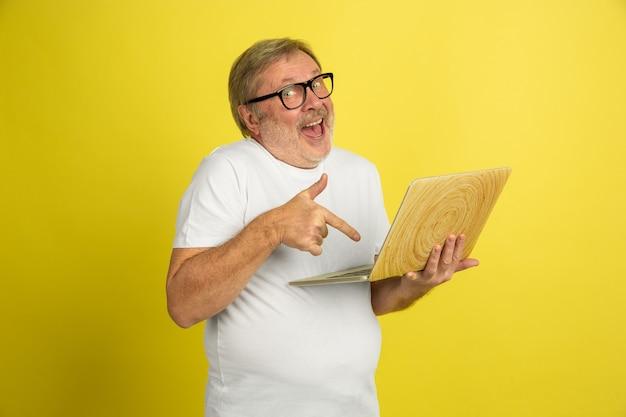 노트북을 사용하여 가리키는. 노란색 스튜디오 배경에 고립 된 백인 남자 초상화입니다. 흰 셔츠 포즈에서 아름 다운 남성 모델입니다. 인간의 감정, 표정, 판매, 광고의 개념. copyspace.