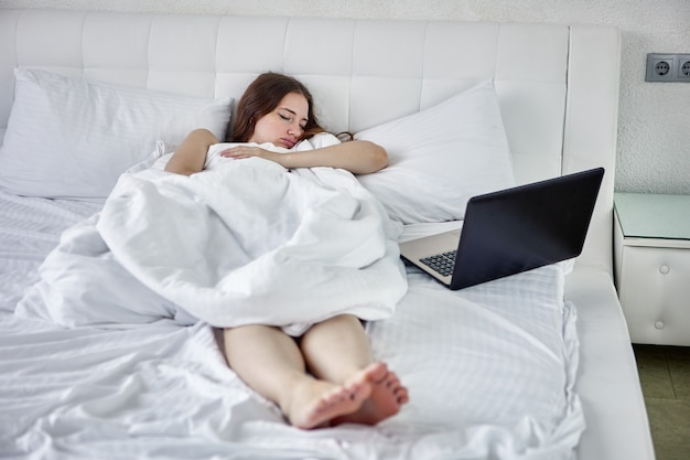 Using laptop to remote working at home a young woman fell asleep while telecommuting online