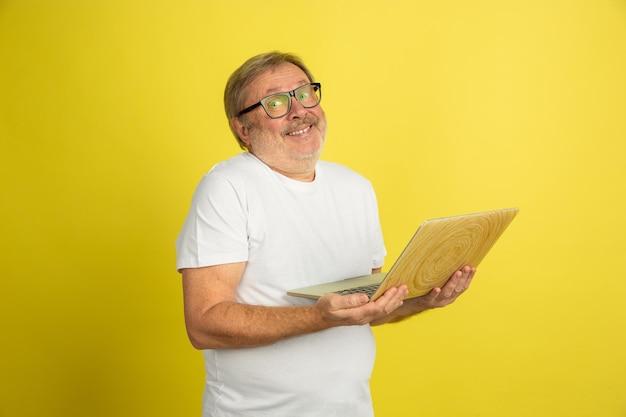 노트북을 사용하여 웃고. 노란색 스튜디오 배경에 고립 된 백인 남자 초상화입니다. 흰 셔츠 포즈에서 아름 다운 남성 모델입니다.