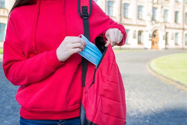 격리 개념 동안 의료 마스크를 사용합니다. 의료용 마스크를 가방에서 들고 있는 캐주얼한 빨간 스웨터를 입은 어린 소녀의 클로즈업 사진