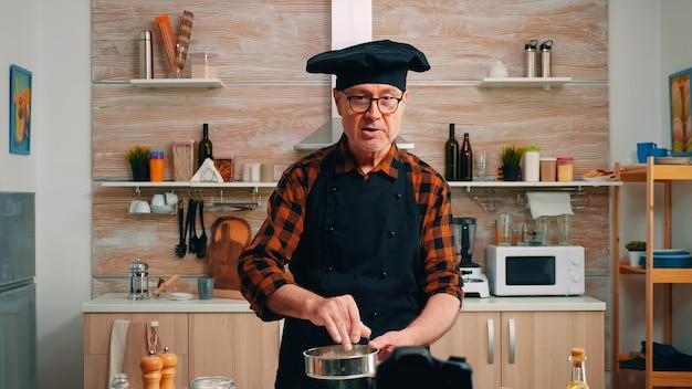 Использование металлического сита во время приготовления пищи для записи нового кулинарного эпизода. блогер на пенсии, повар, влиятельный человек, используя интернет-технологии, общается со съемками в блогах в социальных сетях с помощью цифрового оборудования