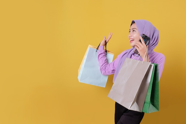 Using mobile phone beautiful asian shopaholic women and credit card holding shopping bags, looking something