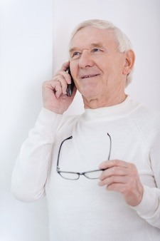 Using modern gadgets. cheerful senior man talking on the mobile phone and holding glasses while leaning at the wall