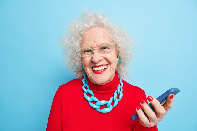 Using modern technologies among all ages. mature positive grey haired woman with bright makeup dressed in red jumper with necklace uses smartphone waits for call smiles positively,.