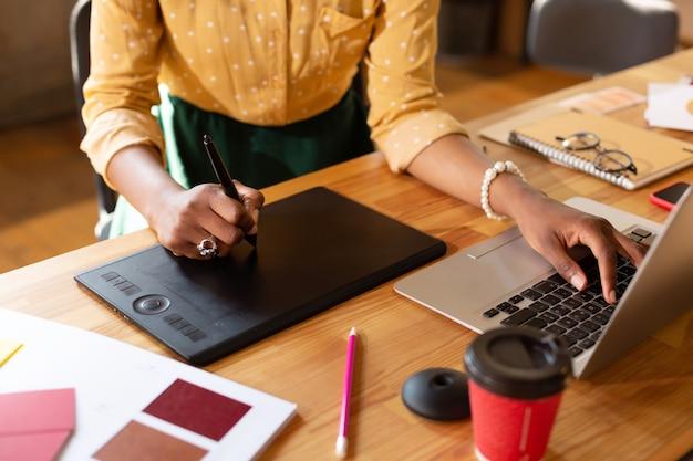 最新のテクノロジーを使用しています。現代の技術を使用して作業している白いブレスレットを身に着けている女性のクローズアップ