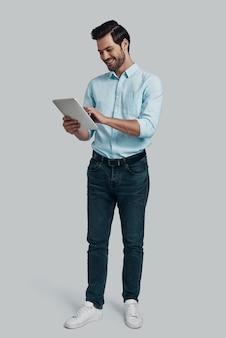 最新のテクノロジーを使用しています。灰色の背景に立っている間デジタルタブレットを使用して作業している若い男の全長
