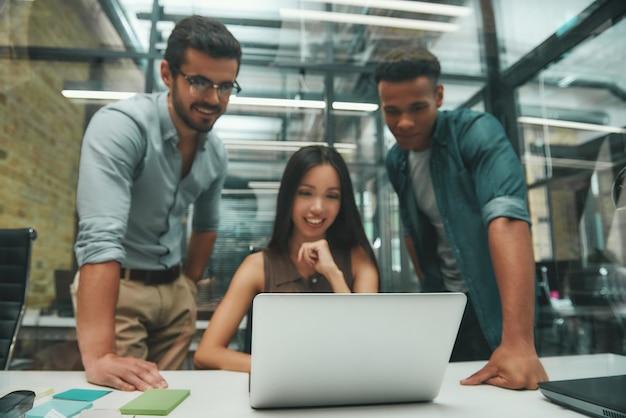 노트북 화면을 보고 있는 3명의 젊고 쾌활한 직원으로 구성된 현대 기술 그룹 사용
