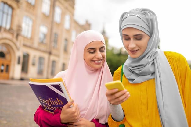 온라인지도 사용. 스마트 폰을 사용하는 두 명의 무슬림 여성이 대학까지 걸어가는 온라인지도 사용