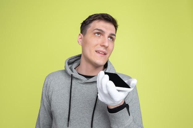 音声に電話を使用する。黄色のスタジオの壁に分離された白人男性の肖像画。手袋を使用した気紛れな男性モデル。人間の感情、顔の表情、販売、広告の概念。異常な外観。