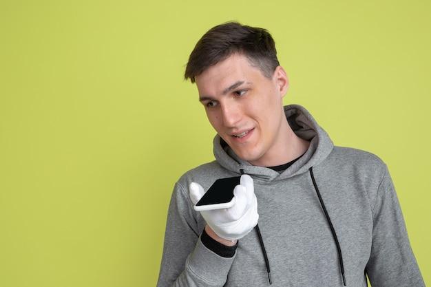 音声に電話を使用する。黄色の壁に分離された白人男性の肖像画。手袋を使用した気紛れな男性モデル。 Premium写真
