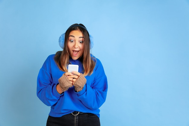 Using phone, happy. caucasian woman's portrait on blue  space. beautiful female model in warm clothes