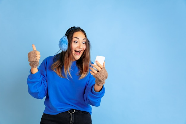Using phone, happy. caucasian woman's portrait on blue studio background. beautiful female model in warm clothes. concept of human emotions, facial expression, sales, ad. winter mood, holidays.