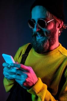 Using phone in sunglasses. caucasian man's portrait on gradient  space in neon light