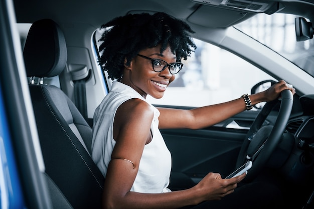 Using phone. young african american woman sits inside of new modern car.