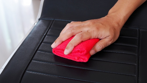 Using red cloth to wipe on chair to clean and prevent germs in house.