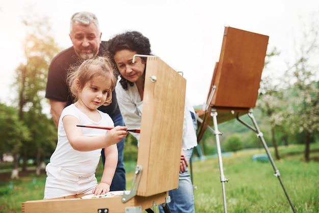 赤い色のブラシを使用しています。祖母と祖父は孫娘と屋外で楽しんでいます。絵画の構想