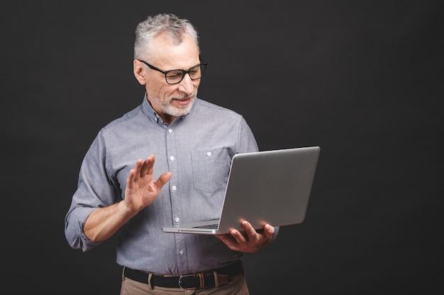 С помощью скайпа. старший пожилой бородатый старик в очках держит портативный компьютер