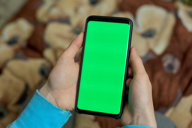 Использование смартфона с зеленым экраном. руки прокручивают страницы, стучат по сенсорному экрану. вид сверху. хроматический ключ