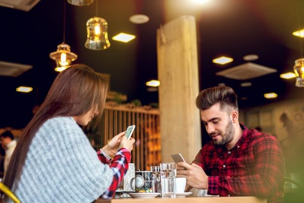 Using smart phones at cafe bar.