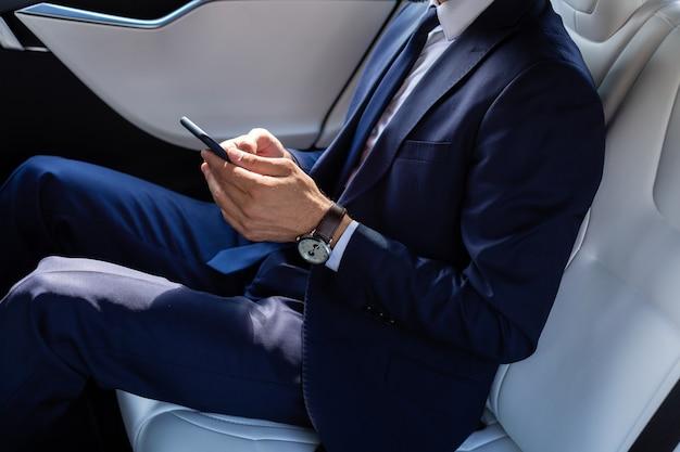 Используя смартфон. крупным планом бизнесмена в костюме с помощью смартфона, сидя на заднем сиденье в машине