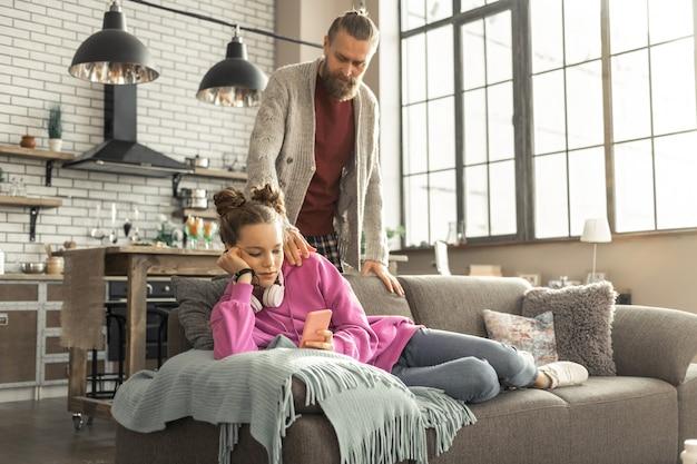 스마트 폰 사용. 딸이 소파에 누워 아버지를 돕는 대신 스마트 폰을 사용