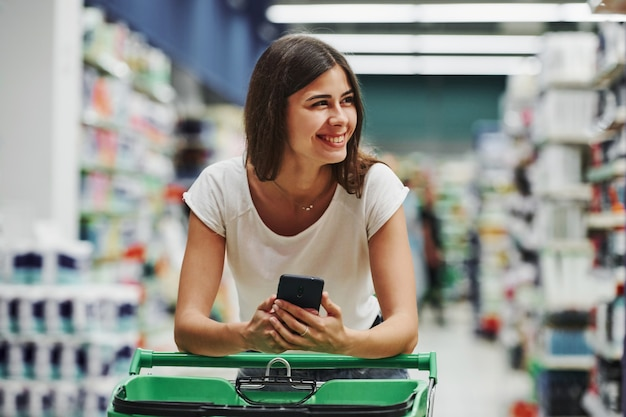 Using smartphone. female shopper in casual clothes in market looking for products.