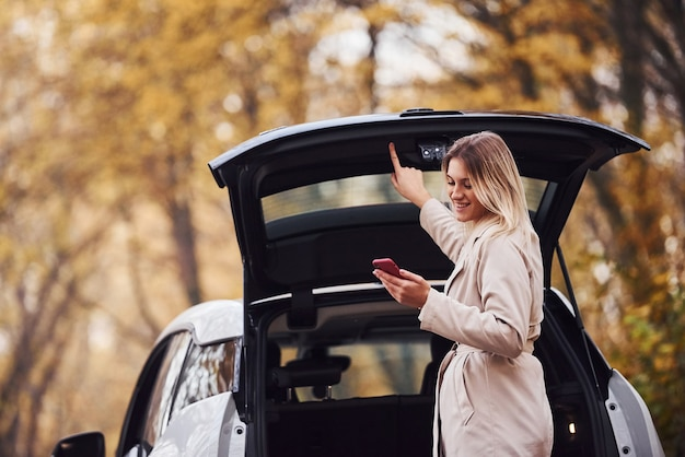 Using smartphone. girl have autumn trip by car. modern brand new automobile in the forest. Premium Photo