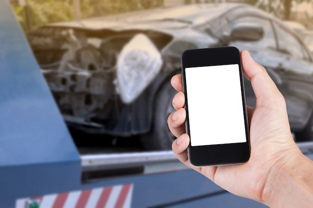 Using smartphone on hand with blurry background of black car on accident on the forklift.