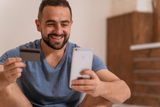 Используя смартфон красивый бородатый парень, держа в руках дебетовую или кредитную карту, покупая онлайн.