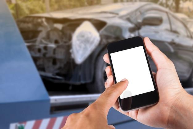 フォークリフトで事故で黒い車のぼやけた背景で手にスマートフォンを使用しています。