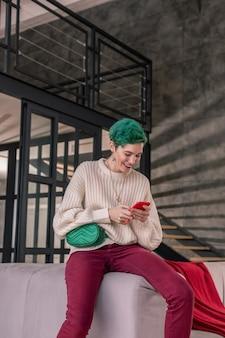 スマートフォンの使用。スマートフォンを使って緑のウエストバッグを着たスタイリッシュな緑の髪の女性