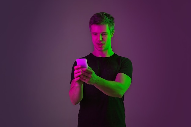 Utilizzando smartphone, prendendo selfie, vlog. ritratto dell'uomo caucasico su sfondo viola studio in luce al neon. bellissimo modello maschile in camicia nera. concetto di emozioni umane, espressione facciale, vendite, annuncio.