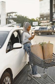 기다리는 동안 스마트폰을 사용합니다. 낮에 전기 자동차 충전소에 아프리카 민족 여자. 아주 새로운 차량입니다.